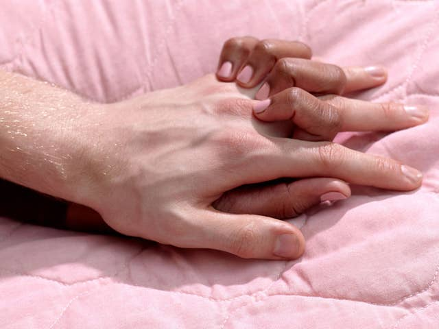 A photo of two people holding hands on a pink bedspread.